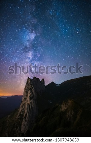 Mountain landscape in the Swiss Alps with jagged peaks and a pristine blue mountain lake in the valley far below. Amazing milky way picture in the swiss alps.