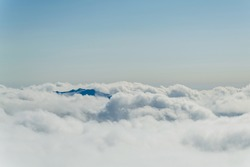 Mountain landscape of Georgia. Snow-capped mountain peak among snow-white cumulus clouds