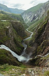 mountain landscape of norway with a waterfall on a background of cloudy sky
