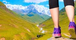 Mountain landscape of Svaneti Georgia - Woman walking (hiking) go up  a snowy mountain - Woman walking sport feet on trail healthy lifestyle fitness