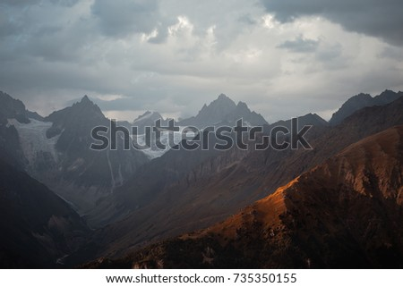 Mountain landscape. Sharp rocks in Georgia. Snow-covered mountains of the Caucasus against the background of a gloomy sky.