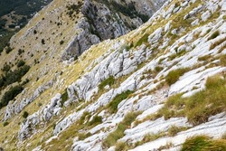 Mountain landscape - steep rocky slope on the hillside with scarce low grass and stones. Topography of a desolate countryside at high altitude.
