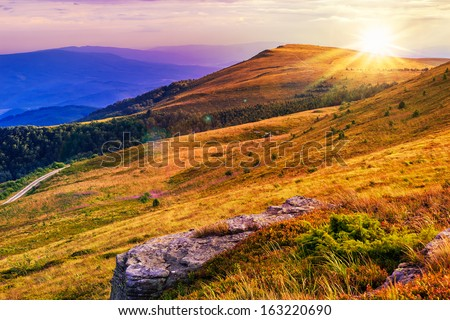 mountain landscape. valley with stones on the hillside. forest on the mountain under the beam of light falls on a clearing at the top of the hill.