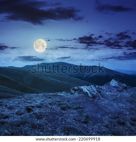 mountain landscape. valley with stones on the hillside. forest on the mountain under the beam of light falls on a clearing at the top of the hill. at night in full moon light