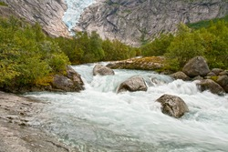 Mountain landscape with a glacier and rough river