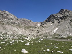Mountain landscape with a high-altitude lake. A mountain range. Sunny weather, blue sky. The Caucasus Mountains.