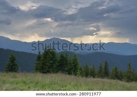 Mountain landscape with bad weather. Summer evening with rain over the top
