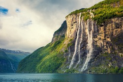Mountain landscape with cloudy sky. Beautiful nature Norway. Geiranger fjord. Seven Sisters Waterfall