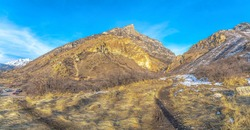 Mountain landscape with grassy slope terrain dusted with fresh snow in winter