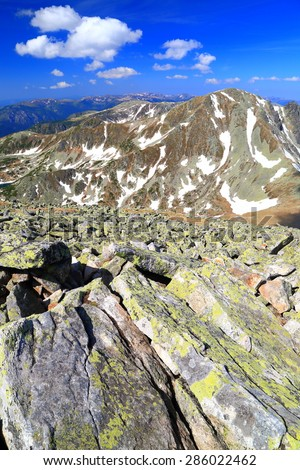 Mountain landscape with large rocks and snow spots in summer