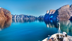 Mountain landscape with reflection.  Expedition cruise ship in Sam Ford Fjord, Baffin Island in Nunavut, Arctic Canada, wide format