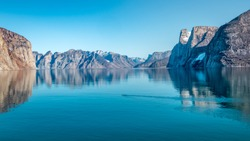 Mountain landscape with reflection. Polar bear  in Sam Ford Fjord, Baffin Island in Nunavut, Arctic Canada, wide format