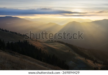 Mountain landscape with Sun behind the clouds producing warm and positive sun rays