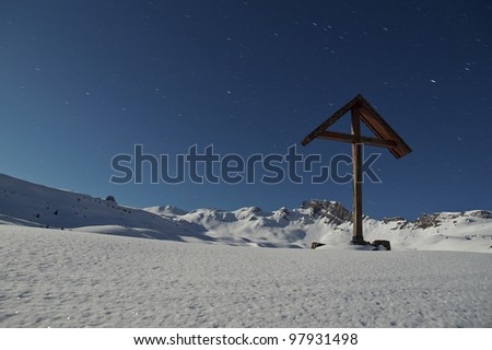 Mountain landscape with wood cross at full moon
