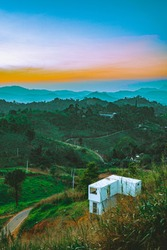 Mountain life beautiful rolling hills and mountainous buildings in sunset landscape