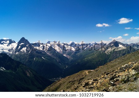 Mountain massif in summer - green forest on the lower slopes, gray rocky peaks in the snow, stony slope in the foreground. #1032719926