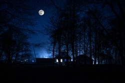 Mountain night landscape of building at forest at night with moon or vintage country house at night with clouds and stars. Cold autumn night
