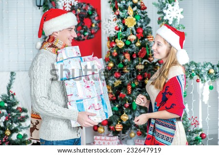 Mountain of gifts. Loving guy gives gifts at Christmas. Young couple in love man and pretty girl wearing sweater and scarf at home