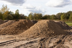 Mountain of sand at a construction site. Foundation material. Soil prepared to strengthen the soil. Earthen heap. Fine sand to create a concrete mortar.