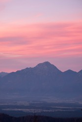 Mountain panorama in the alps at a colorful sunset or sunrise with pink and orange clouds in the sky building contrasts and layers