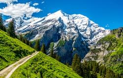 Mountain path to snow topped peak landscape