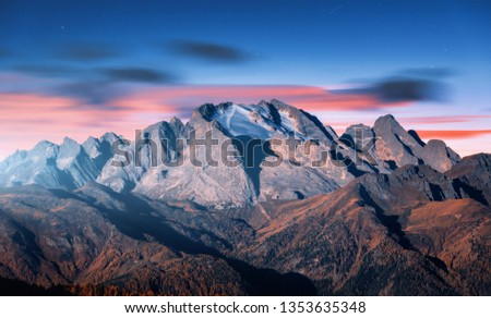 Mountain peak lighted by moonlight in autumn at night in Dolomites, Italy. Beautiful landscape with mountains, forest on hills, blue sky with pink clouds, stars at dusk. Italian alps. High rocks #1353635348
