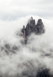 Mountain peak peeking through the clouds in the Dolomites