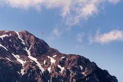 Mountain peak with snow patches and para glider flying above. Mountaineering, extreme sports and nature concepts.