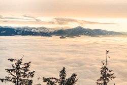 Mountain peaking through cloud inversion during sunset orange sky in Orava Region, Slovak republic. Travel destination. Tatry  in the background. Winter inversion clouds