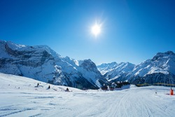 Mountain peaks and clean empty ski trails in Pralognan-la-Vanoise range over snowy tops in French Alps