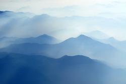 mountain peaks in morning fog - foggy morning over Italian mountains near Milan