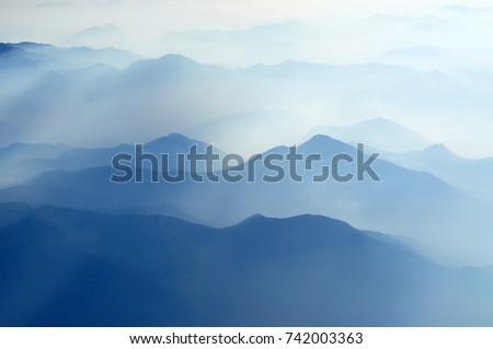 Stock Photo mountain peaks in morning fog - foggy morning over Italian mountains near Milan