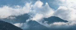 Mountain peaks in the clouds. Panoramic view.