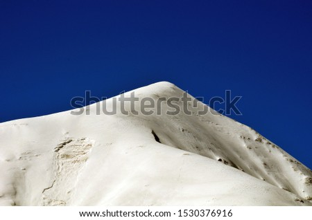 Mountain peaks, peaks covered with snow and forest against a clear sky.