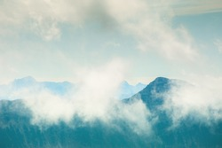 Mountain peaks with clouds in foggy morning. Beautiful nature background. Vintage filter