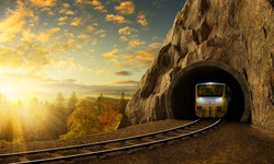 Mountain railroad with train in tunnel. Sunset landscape under the big rock.