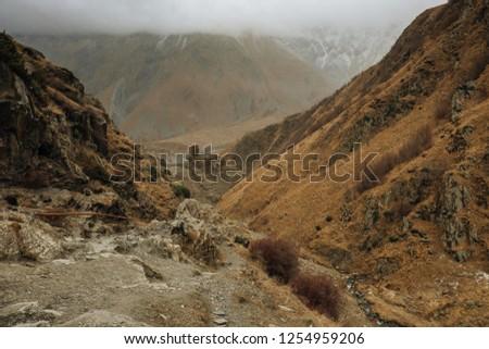 Mountain range on a hiking trail from Stepantsminda to Gergeti Trinity Church. a famous landscape in Kazbegi, Mtskheta-Mtianeti, Georgia. #1254959206