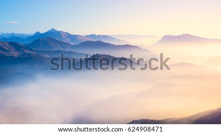 Mountain range with visible silhouettes through the morning colorful fog. #624908471