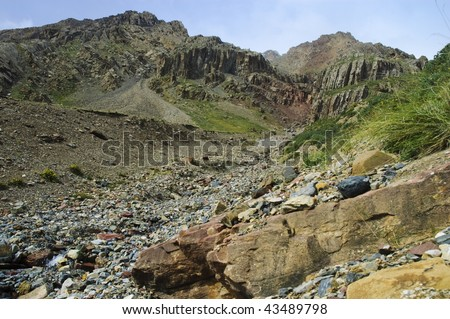 Mountain ravine with a stream and lots of multicolored stones. Terskey mountains, Central Tien-Shan, Kyrgyzstan.