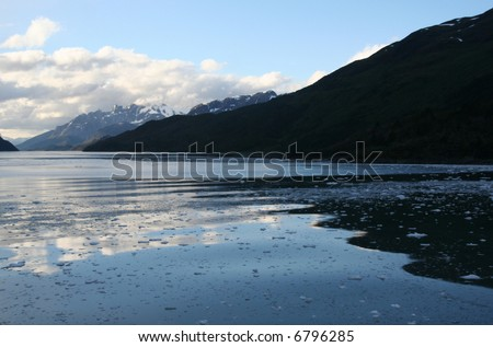 Mountain reflection with brash ice forming at sundown in calm glacier bay,	Strait of Magellan, 	Patagonia,	Chile