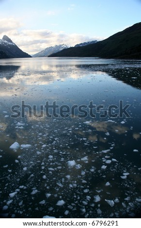Mountain reflection with brash ice forming at sundown in calm glacier bay,Strait of Magellan, Patagonia,Chile