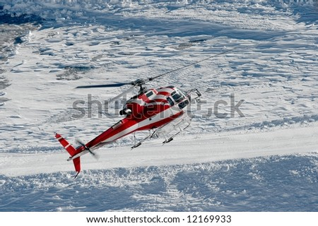 Mountain rescue helicopter flying in a snowy mountain range