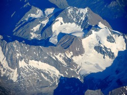 Mountain resembling a face side view outlined by surrounding Alps range shadows