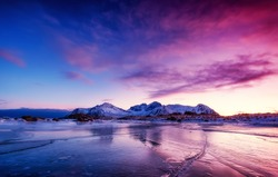 Mountain ridge and ice on the frozen lake surface. Natural landscape on the Lofoten islands, Norway. Water and mountains during sunset.