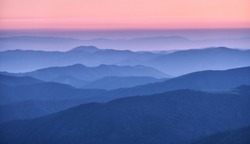 Mountain ridges in fog at sunset in autumn. Beautiful landscape with foggy mountain valley, rocks, forest, pink sky in fall at dusk in blue hour. Aerial view of hills. Top view. Nature background