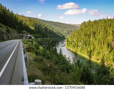 Mountain river and mountain road with tunnel entrance in Norway