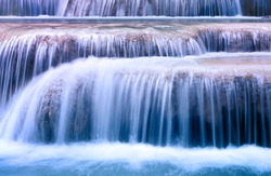 Mountain river background with small waterfalls in tropical forest. Clean blue water flows on cascades of Erawan park in Thailand