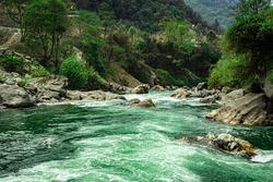 mountain river extreme water flow at forests in day long exposure shot image is taken at dirang river tawang arunachal pradesh india.