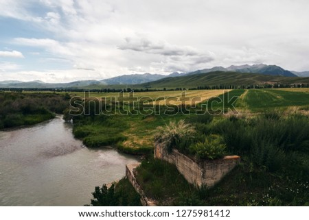 Mountain river in the mountain valley with green valleys, glacier peaks, and blue sky in Kyrgyzstan