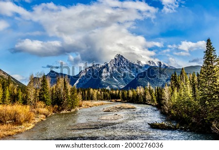 Mountain river on the background of a mountain peak. River valley in mountains. Mountain river valley panorama